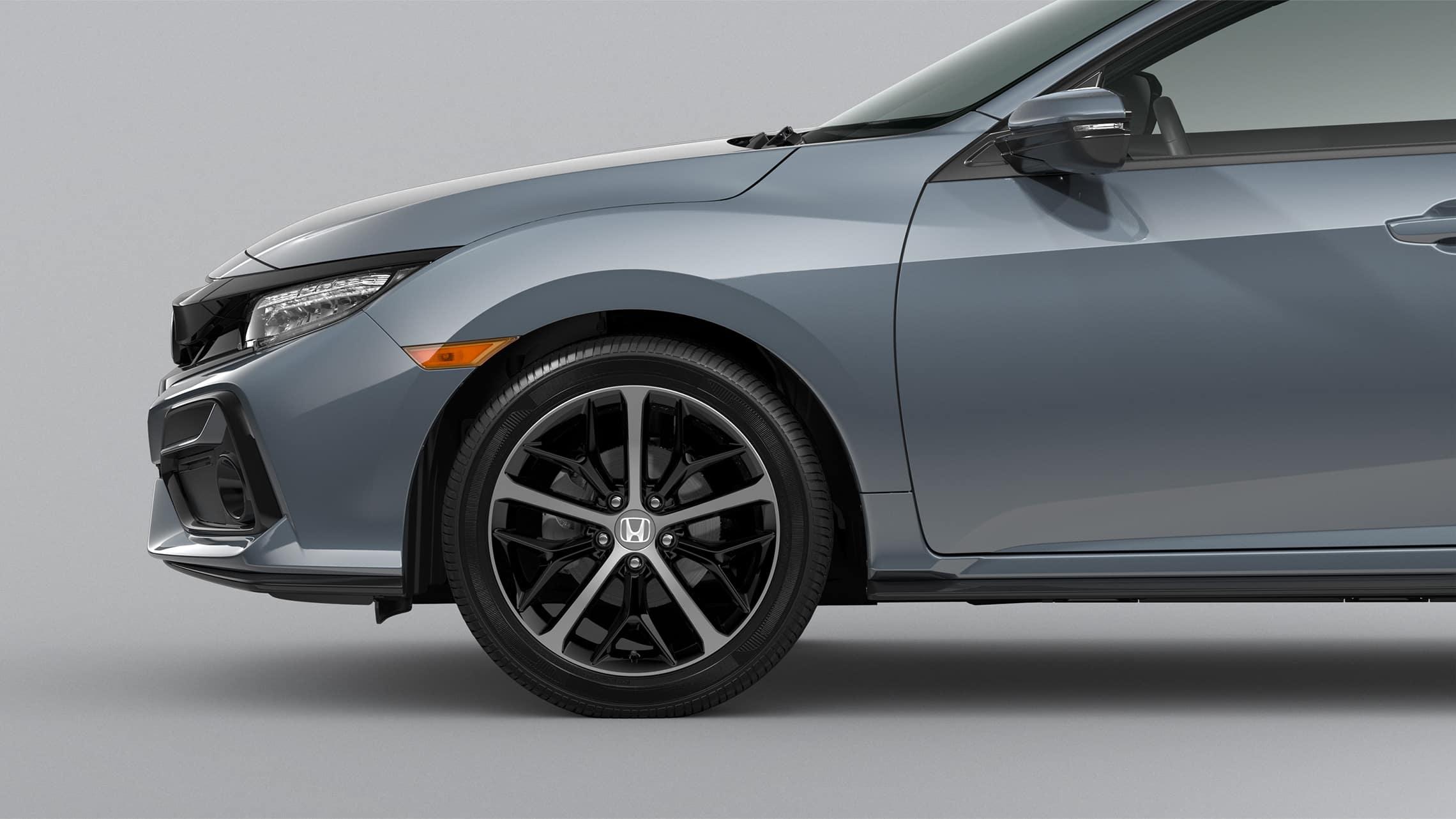 Detalle frontal de ruedas de aleación de 18pulgadas del lado del pasajero en el Honda Civic Sport Touring Hatchback2021 en Sonic Gray Pearl.