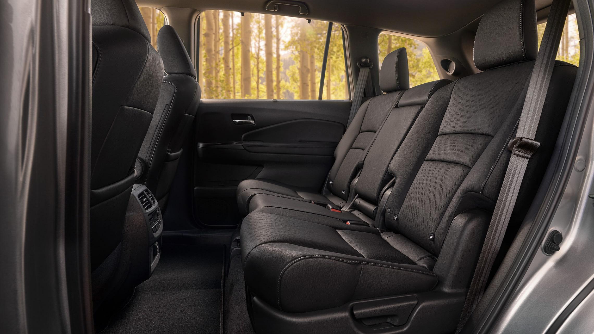 Vista de perfil desde el lado del conductor de los asientos de la segunda fila de la Honda Passport Elite 2021 con cuero Black.
